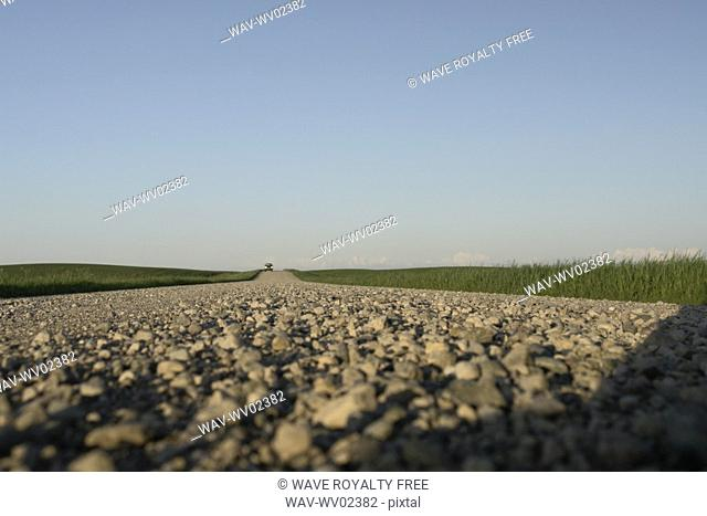 Extreme low angle of graveled country road with oncoming vehicle, Canada, Manitoba, Erickson