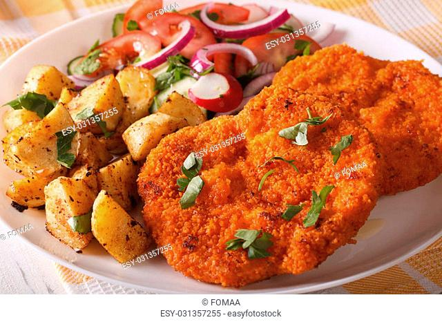 Delicious dinner: Wiener Schnitzel, fresh salad and fried potatoes on a plate close-up. horizontal