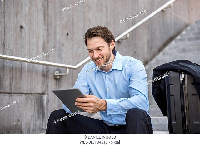 Smiling businessman with rolling suitcase sitting on stairs using tablet