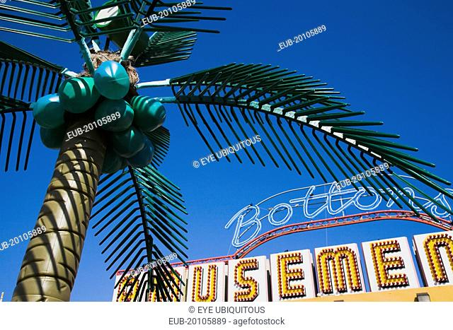 Plastic artificial Palm Tree with amusement arcade behind in clear blue sky