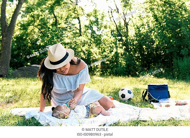 Mid adult woman relaxing with baby son on picnic blanket in Pelham Bay Park, Bronx, New York, USA