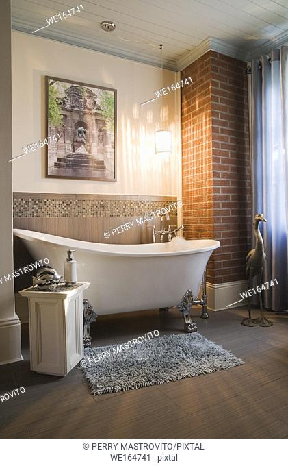 White porcelain claw foot bathtub in the main bathroom inside an old 1877 cottage style residential home, Quebec, Canada