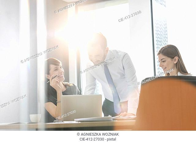 Business people working at laptop in sunny conference room meeting