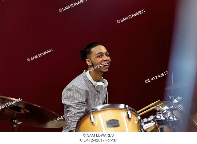 Happy teenage boy musician playing drums in sound booth