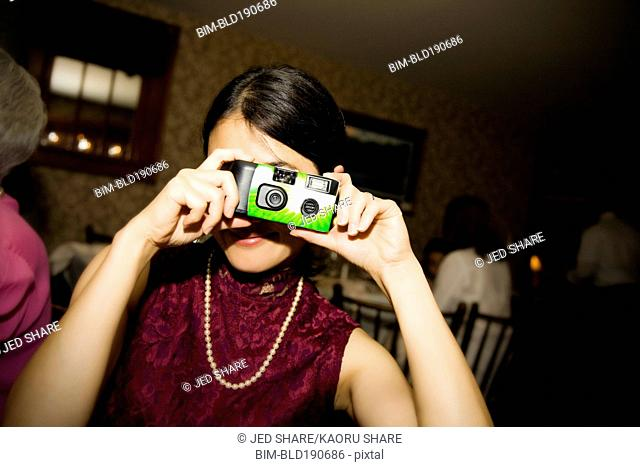 Asian woman taking photograph