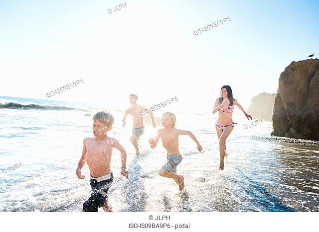 Family playing on El Matador Beach, Malibu, USA