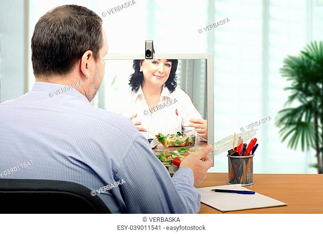 Two office workers are eating takeaway vegetable salad in front of each other by online. They are healthy eating fans