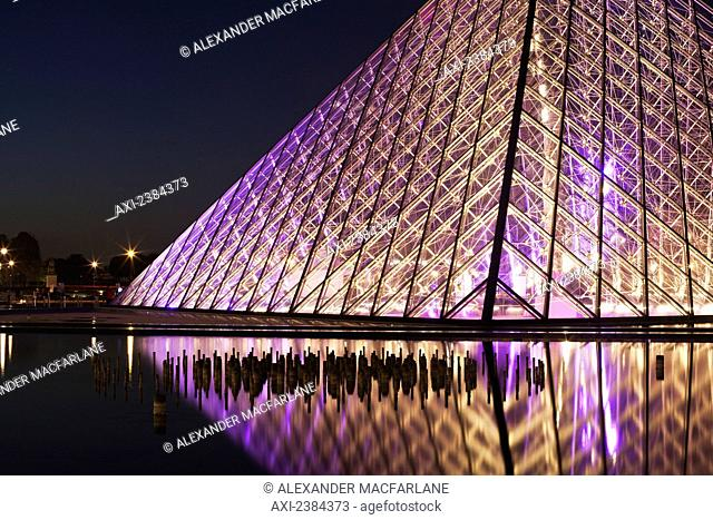The illuminated glass pyramid at the Louvre museum on the water's edge at nighttime; Paris, France