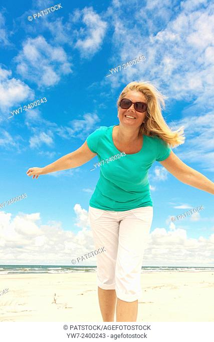 Happy woman on a Baltic sea beach in Poland