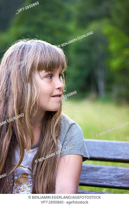 side profile of girl sitting on a bench in nature