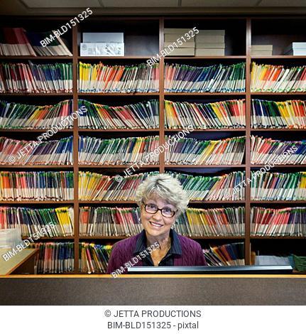 Caucasian medical receptionist sitting near wall of files