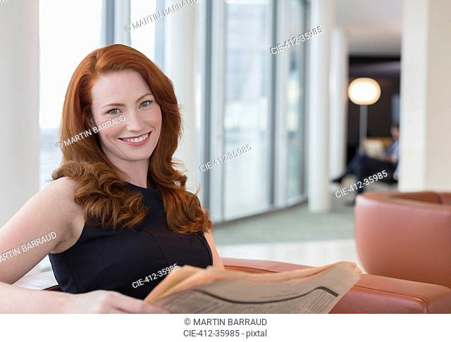 Portrait smiling businesswoman with red hair reading newspaper in office lounge