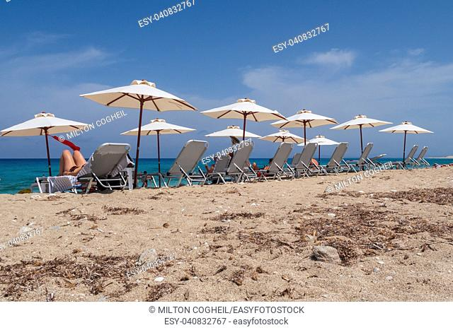 Tourists relaxing on sunlounger on the beach on Lefkada island, Greece