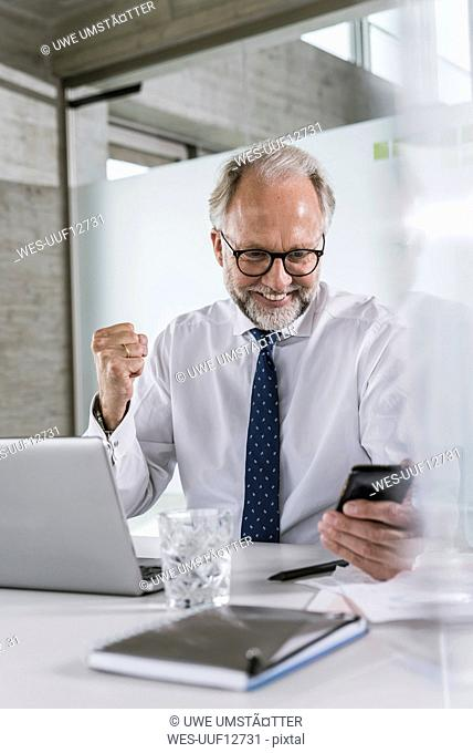 Happy mature businessman at desk in office looking at cell phone