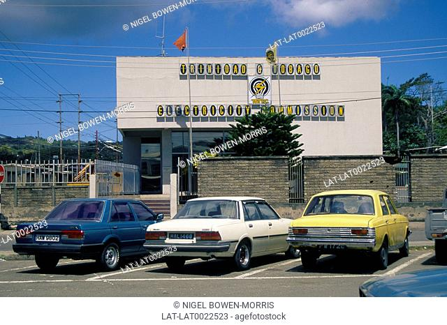 Trinidad and Tobago Electricity Commission building. Cars parked in foreground. Walls. No entry sign
