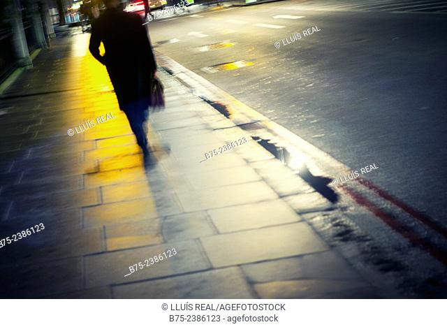 Executive silhouette of a man walking down the street with a briefcase in hand, London, England, UK
