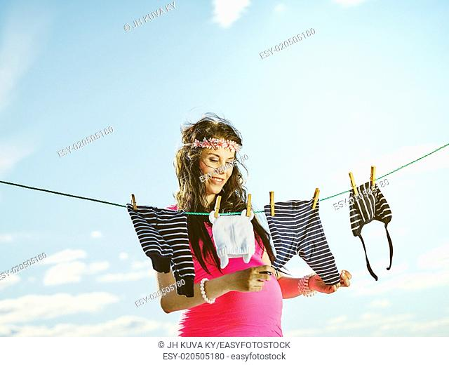 Beautiful pregnant young woman feeling lovely, children clothes on clothesline