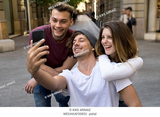 Three happy friends taking a cell phone selfie in the city