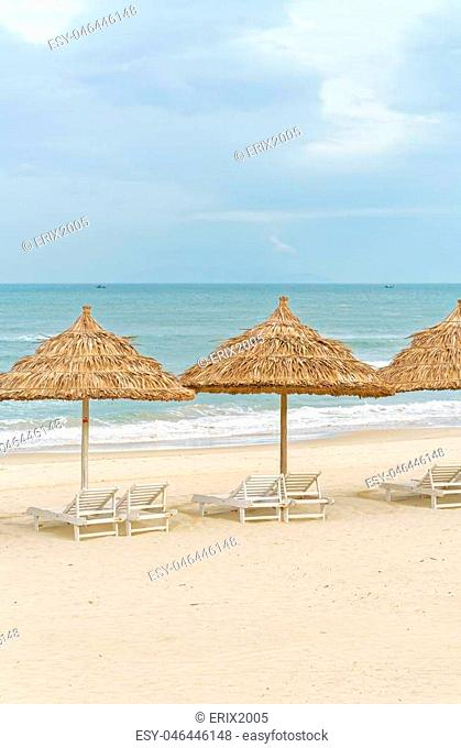 Palm shelter and sunbeds on the China Beach in Da Nang, Vietnam. It is also called Non Nuoc Beach. South China Sea on the background