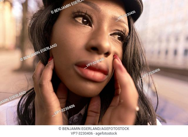 headshot of emotional woman in evening sunlight at street squinting aside, African Angolan descent, in city Munich, Germany
