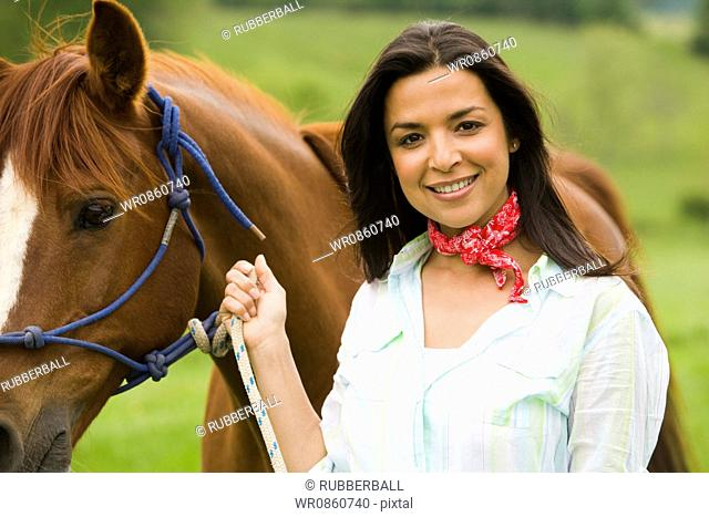 Portrait of a woman holding the reins of a horse