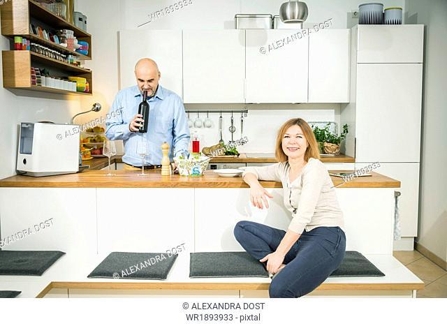Senior man smelling wine cork in kitchen