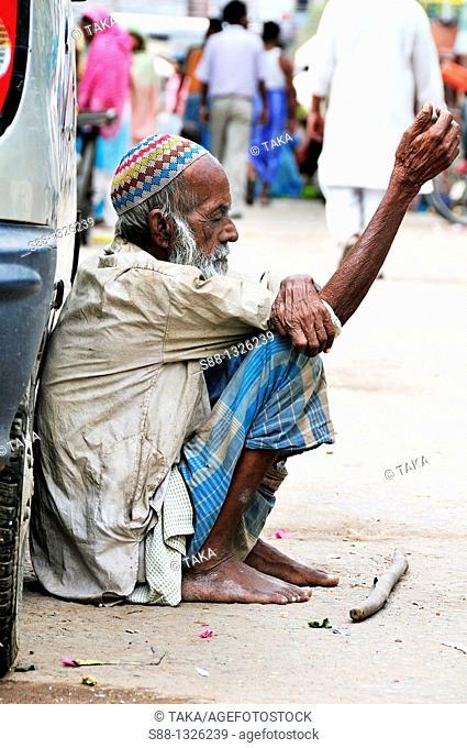 Old man sitting on the road in Old Delhi, Delhi India