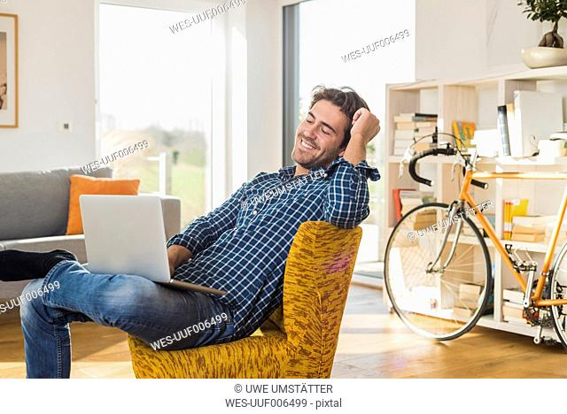 Portrait of smiling young man sitting on armchair in the living room with laptop