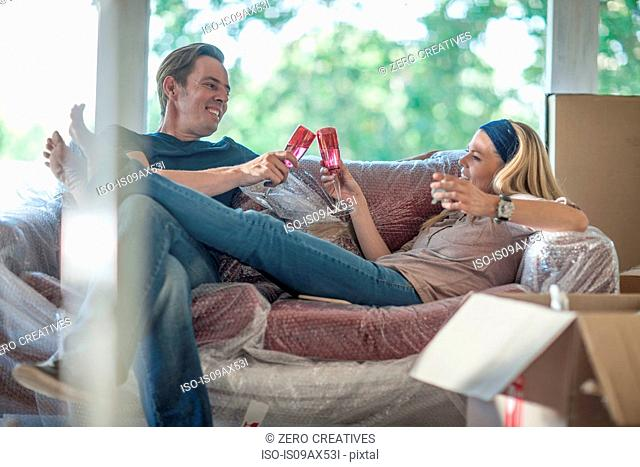 Moving house: couple relaxing on bubbled wrapped sofa, in room with cardboard boxes, holding champagne flutes, making a toast