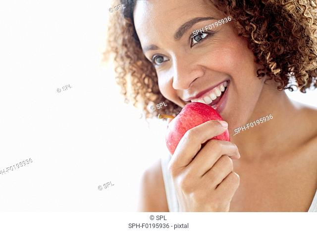 Mid adult woman eating apple