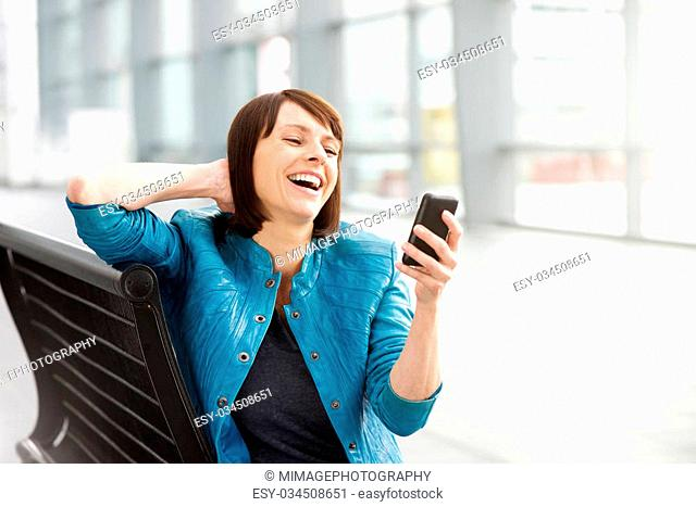 Portrait of an older woman reading text message and laughing
