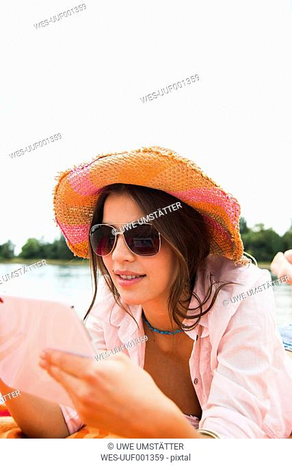 Portrait of smiling young woman with summer hat and sun glasses using digital tablet