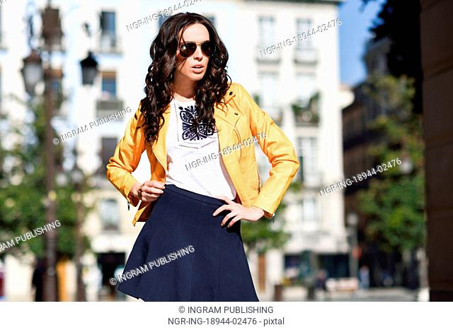 Young brunette woman with sunglasses. Girl, model of fashion, wearing orange modern jacket and blue skirt, standing in urban background