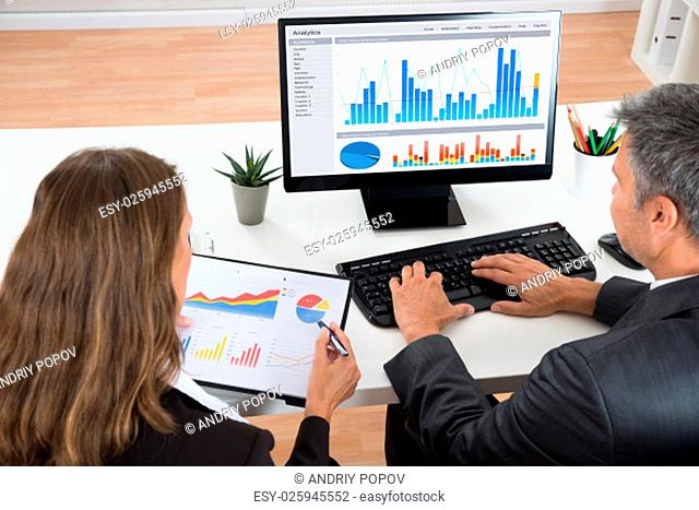Two Businesspeople Analyzing Graphs At Desk In Office