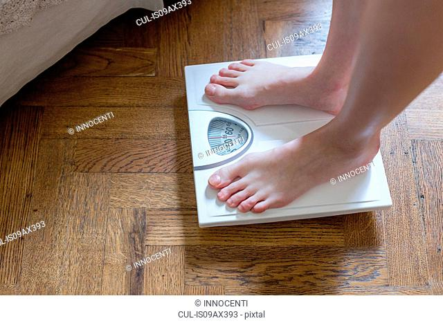 Womans feet standing on bathroom scales