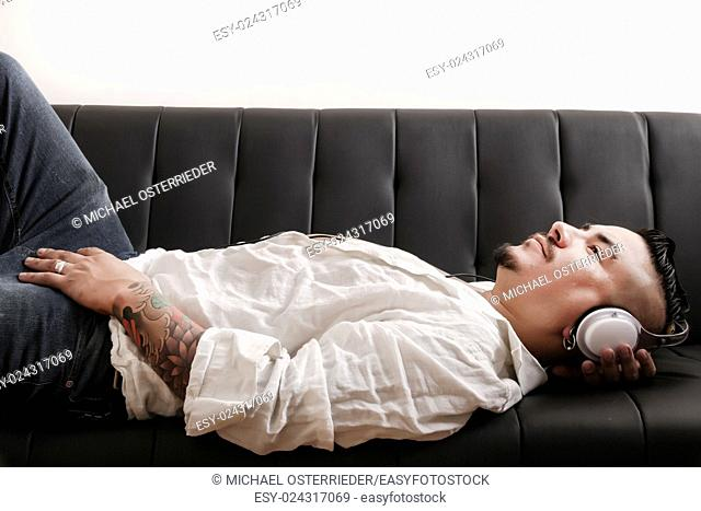 A tattooed hispanic man listening to music while lying on the sofa.
