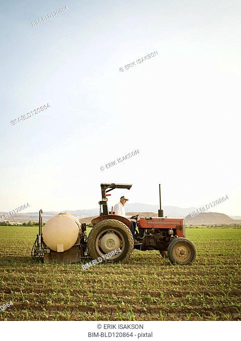 Caucasian farmer driving tractor in crop field