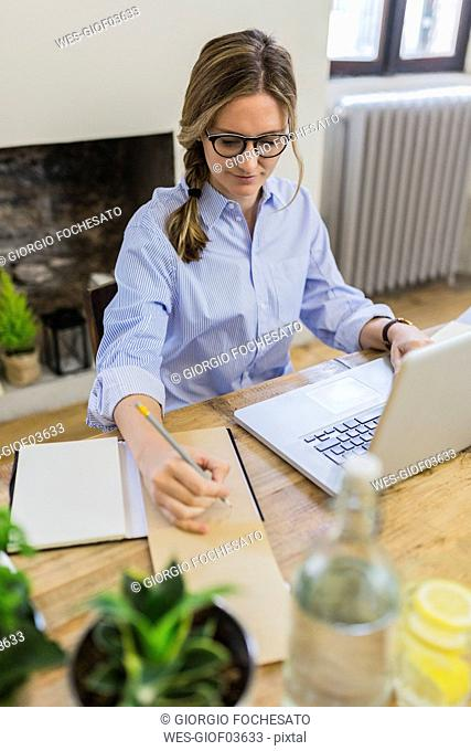 Woman using laptop and taking notes on wooden desk at home