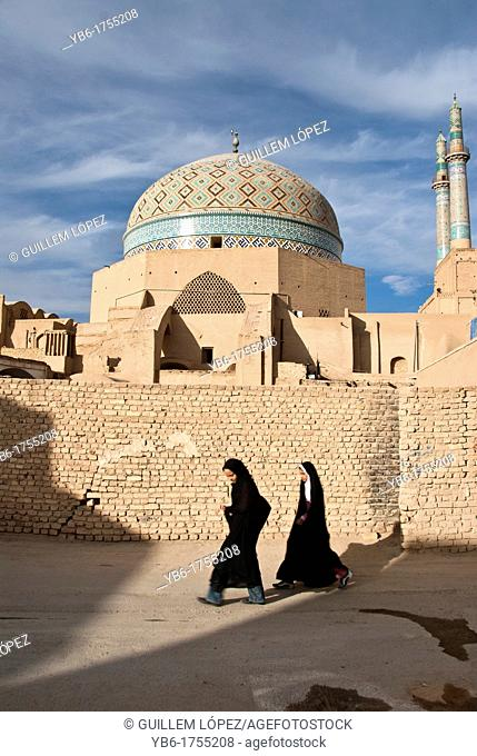Children wearing Hijab walking in front of the Jameh Mosque of Yazd, Iran
