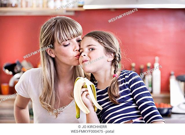 Germany, North Rhine Westphalia, Cologne, Girl eating banana while mother kissing