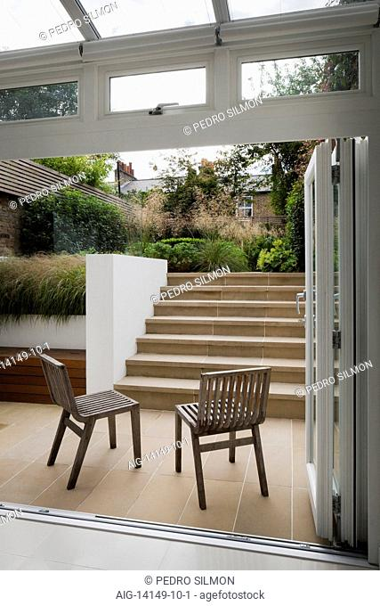 French windows open onto the lower York stone paved outside area, with benchstore and York stone steps leading up to the larger, upper level