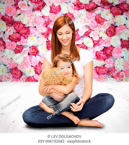 childhood, parenting and relationship concept - happy mother with adorable little girl and teddy bear