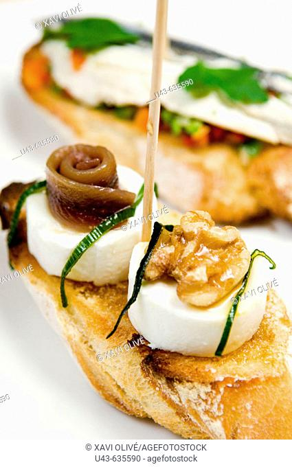 'Montaditos'. Spanish canapé: cheese with nuts and marinated anchovies