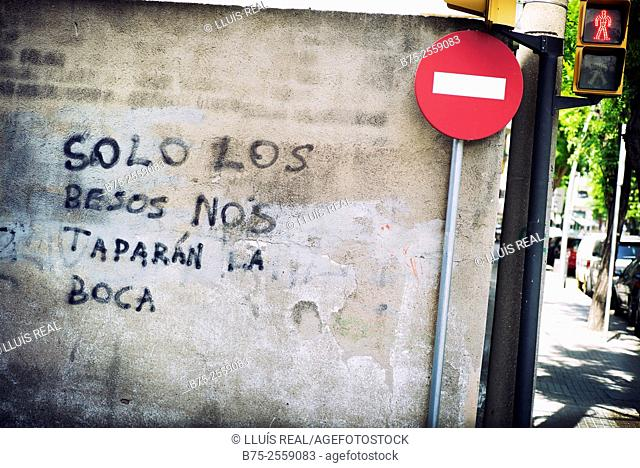 Solo los besos nos taparán la boca. Graffiti written on a wall with a traffic sign post of no trespassing. Barcelona, Spain, Europe