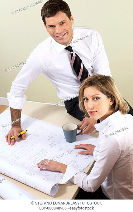 Businesspeople working on blueprints