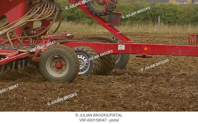 sowing wheat, panning shot in close up following a seed drill