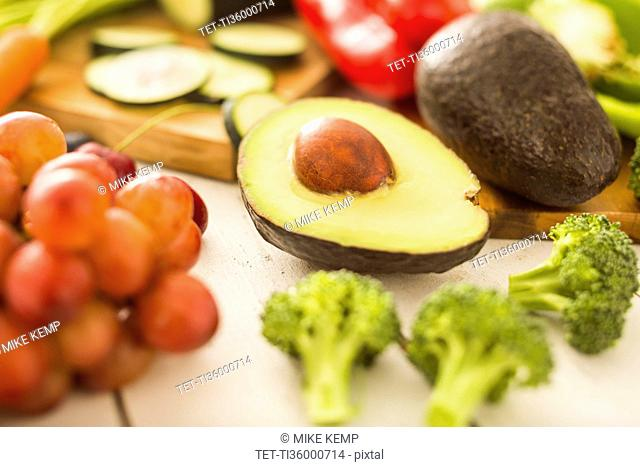 Avocado surrounded by various fruits and vegetables