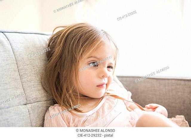 Toddler girl making a face on sofa