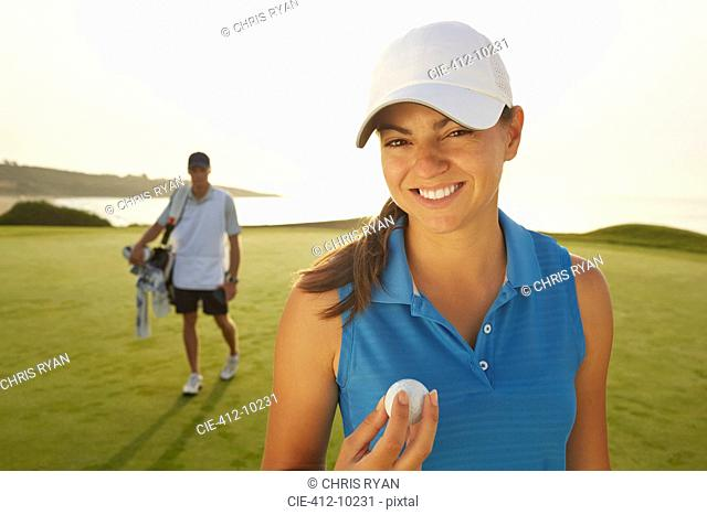 Woman holding golf ball on course
