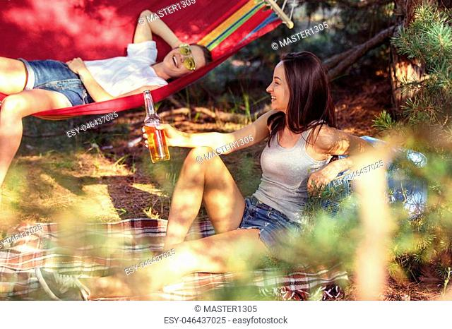 Party, camping of men and women group at forest. They relaxing and eating barbecue against green grass. The vacation, summer, adventure, lifestyle